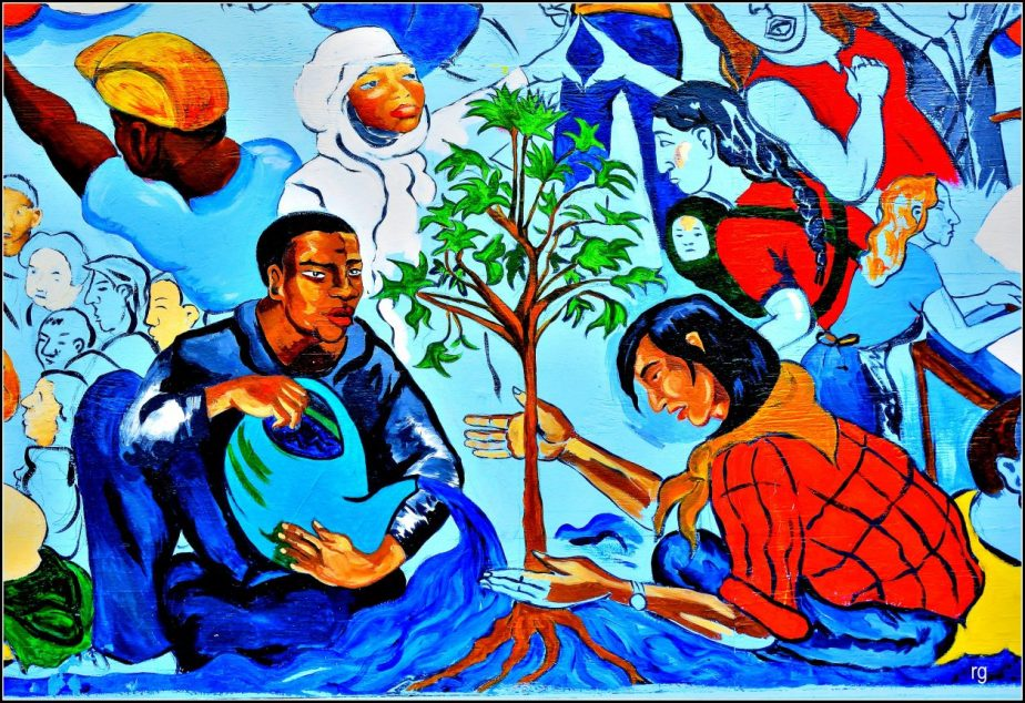 A section of wall mural depicting two men planting a seedling.
