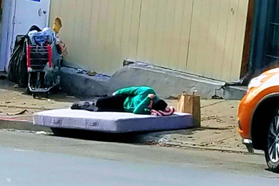Photo of a Homeless woman sleeping on a mattress on Haight Street in San Francisco, November 22, 2016