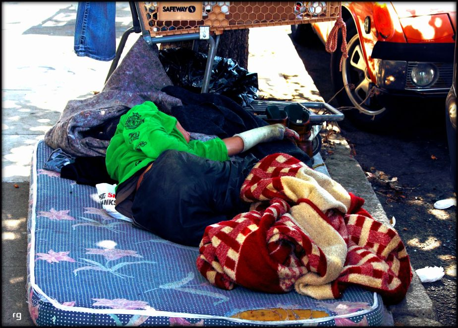 Photograph of a disabled homeless man with his arm in a cast sleeping on a filthy mattress on a street in San Francisco