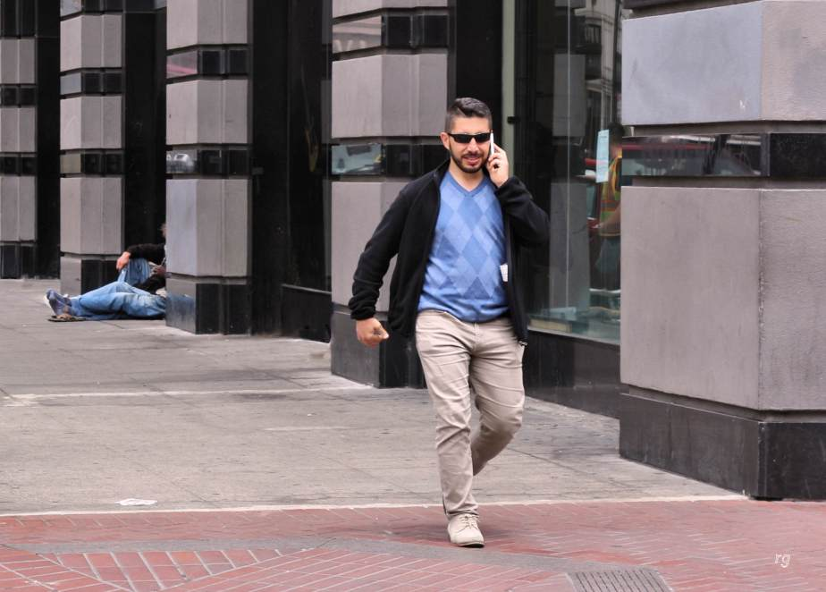 A young well dressed man on a cell phone passes a homless man sitting on the sidewalk in San Francisco.