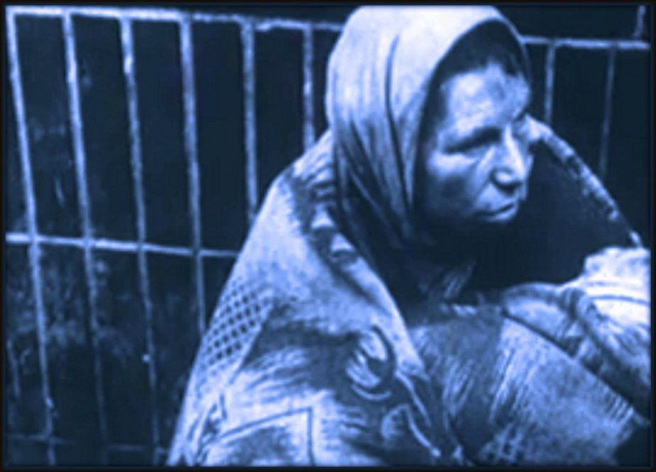 Screen shot of a woman huddled in filthy rags from footage of Nazi Atrocities in the Warsaw Ghetto