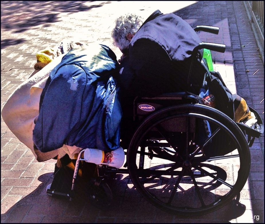 An elderly and disabled man sits homeless in a wheel chair on Market Street in San Francisco