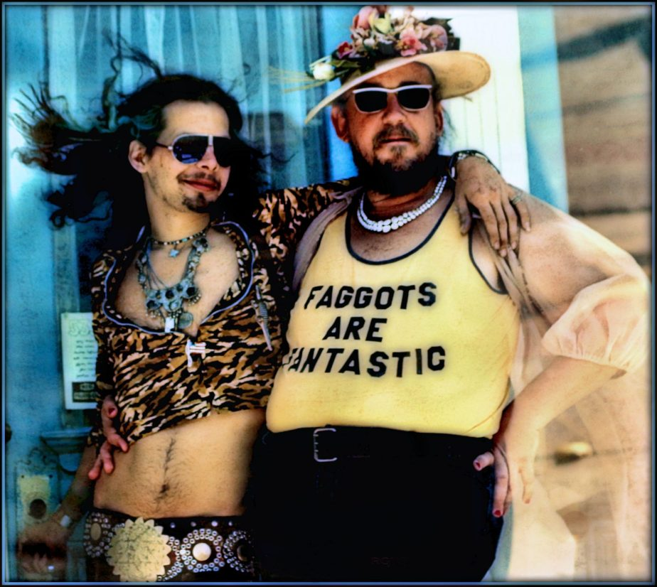 Photograph of a photograph taken in 1976 of two long haired men, one wearing a tee shirt that reads Faggots are fantastic