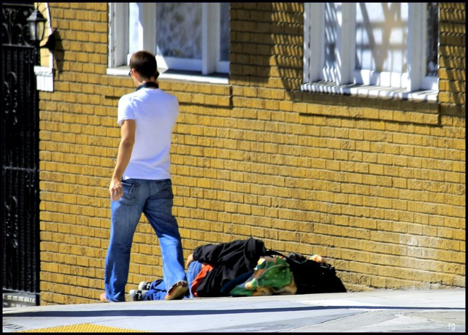 Photograph of a young man on a cell phone strolling past a homeless man asleep under a bundle of rags