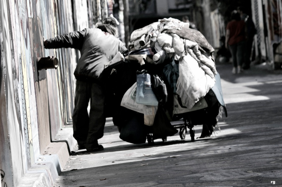 Photograph of an elderly homeless man staggering as he pushes a heavy shopping cart through Clarion Alley in San Francisco