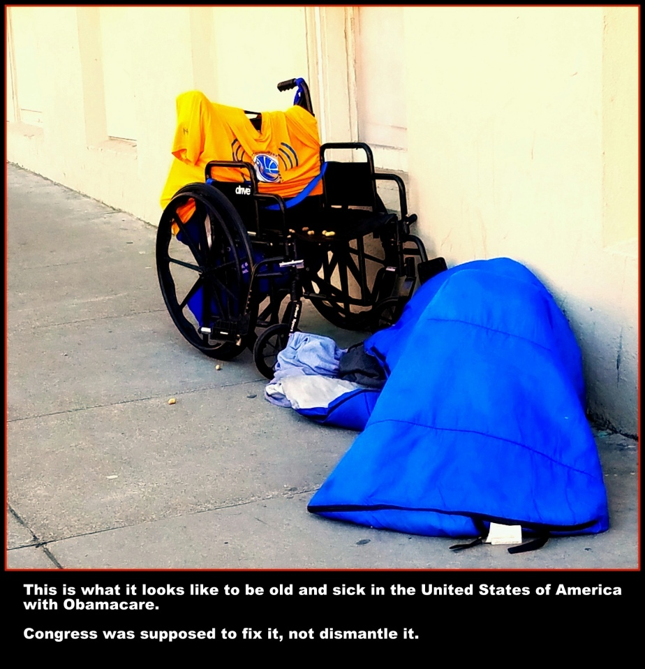 photograph of a homeless disabled person sleeping under a blanket next to his wheelchair