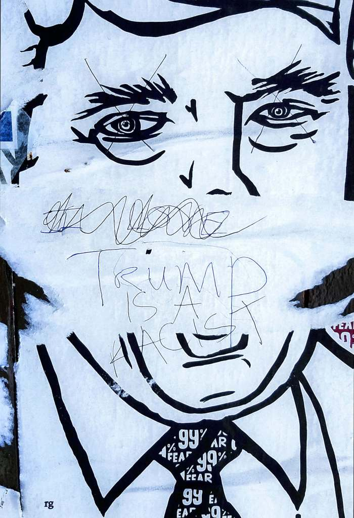 A graffit sticker of Donald Trump with an anus for a mouth with 'Trump is a Racist' scrawled in pen
