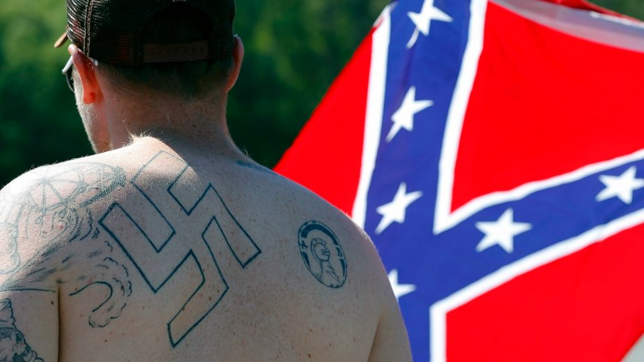 Public domain photo of a man who wears a Swastika in front of a Confederate Flag