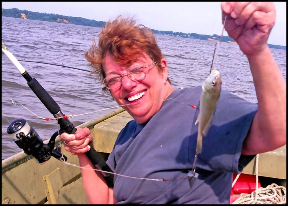 Photograph of Sandra Sarah Goldstein - Dunaway on a 2016 fishing trip. She is laughing and showing off her catch