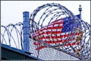 Image of an American Flag behind Barbed Wire