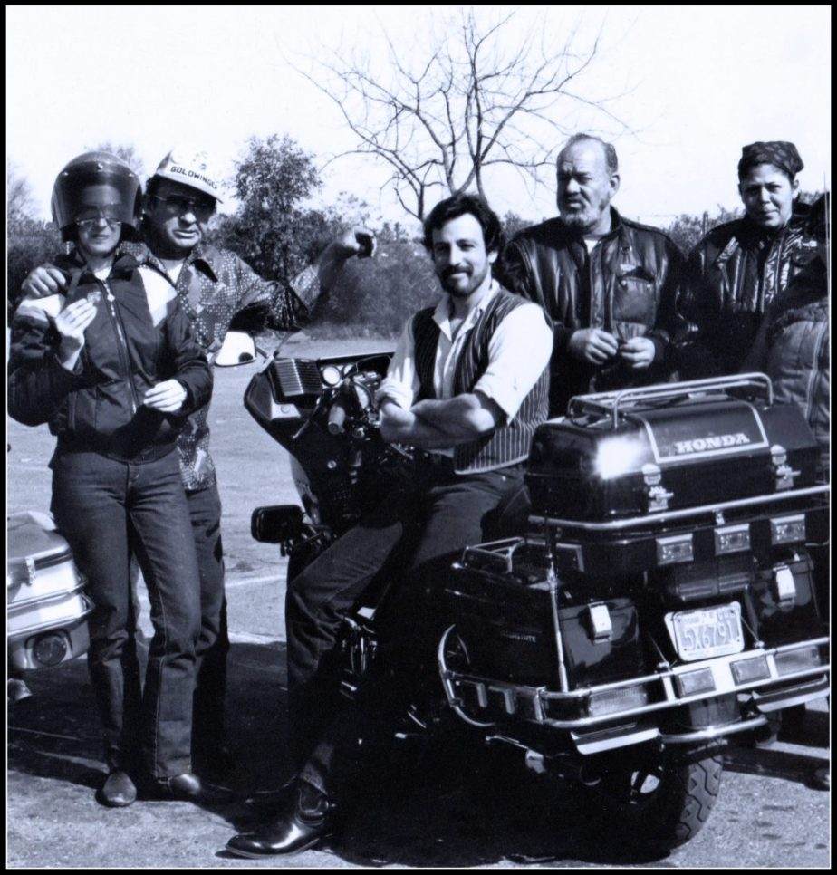 A Photograph of a young man in his early thirties surrounded by members of a motorcycle gang. Taken by phoographer Nina Glaser in 1985
