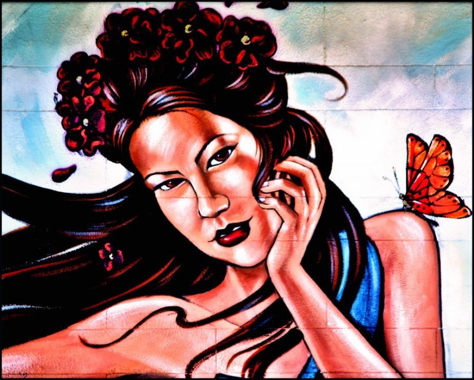 Detail of a wall mural in San Francisco's Mission District depicting a windblown portrait of a young woman of Asian descent