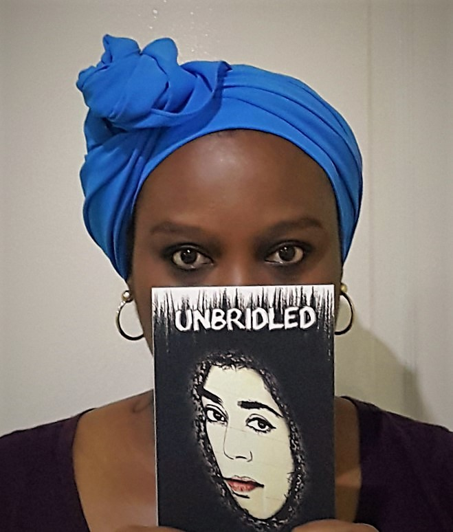 Photograph of blogger Jacqueline Oby-Ikocha holding a copy of her book of poems, 'Unbridled'