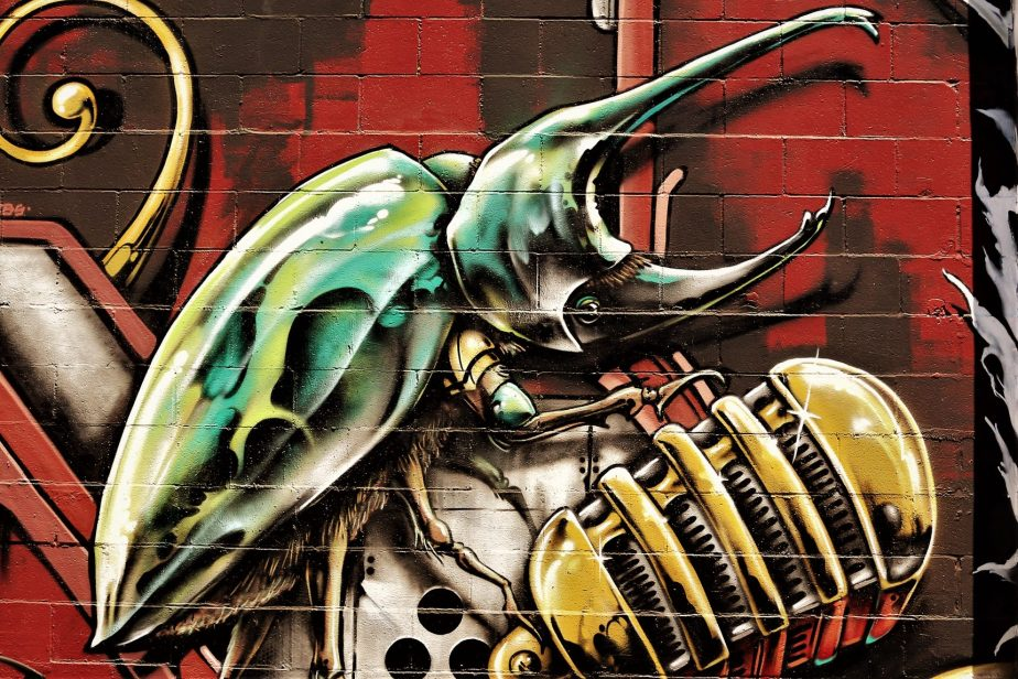 Section of a wall mural on Valencia Street in San Francisco that depicts a dung beetle crawling on a microphone