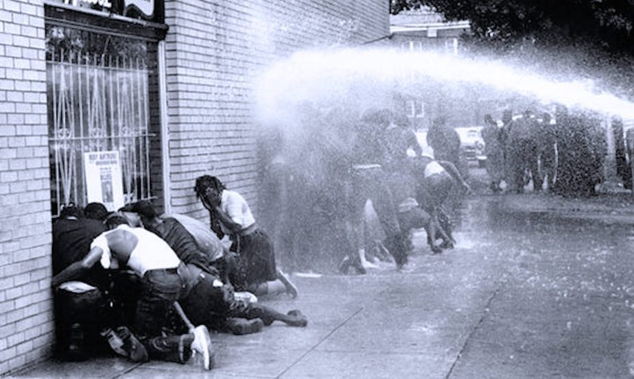 A shot of police turning firehoses on demonstrators in 1963