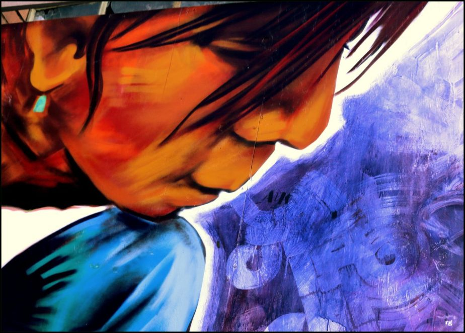 Detail from a Mural in San Francisco's Mission District. It depicts the face of a boy looking with curiosity at something in his hand