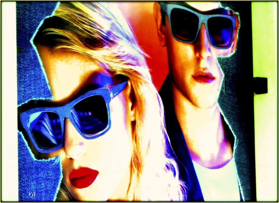 Digitally processed photo of an ad in a shop-window in downtown San Francisco that shows two young androgynous models in sunglasses and makeup