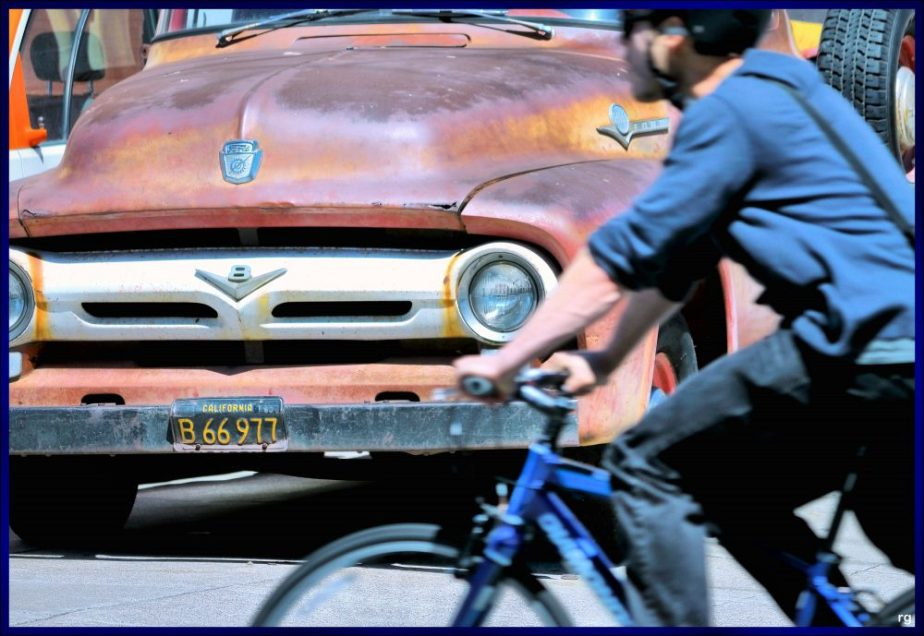 Photograph of a young Bicyclist passing a rusted old car from the 1950's