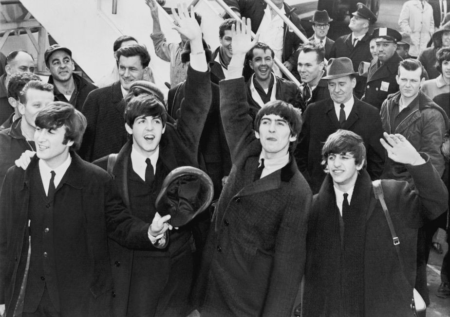 English: The Beatles wave to fans after arriving at Kennedy Airport.