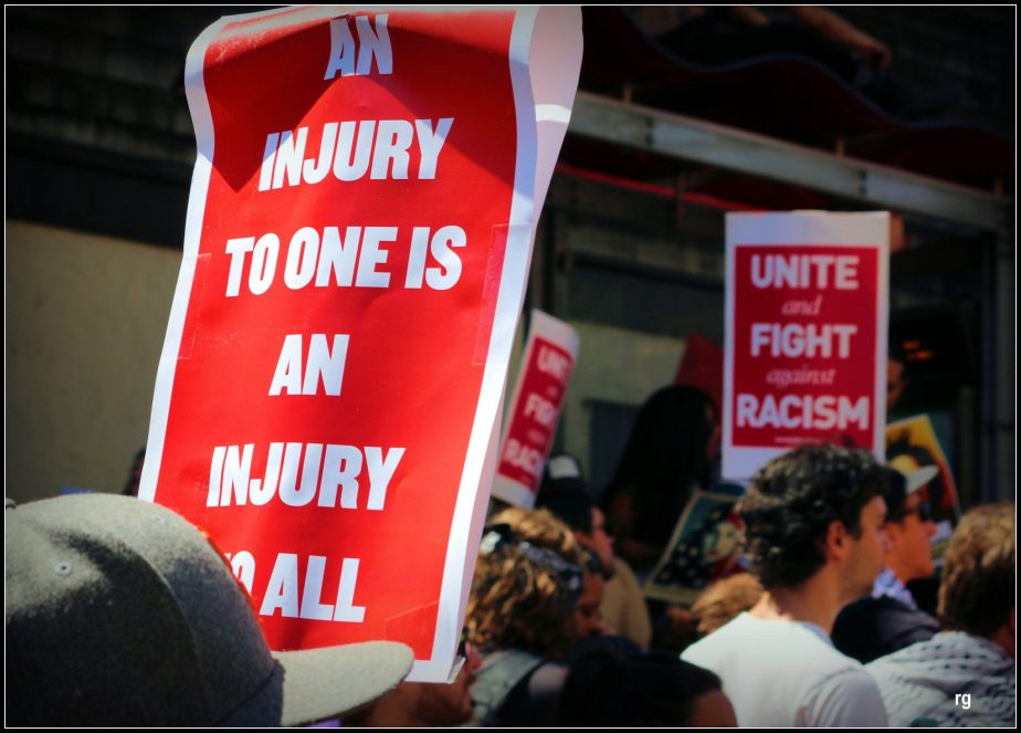 Photyograph of a sign at an anti-Trump Rally which reads an Injury to one is an Injury to all