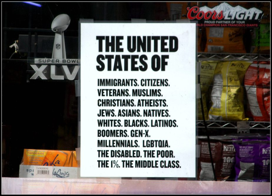 Sign in a shop window that enumerates the diverse cultures of people who call themselves citizens of the United States