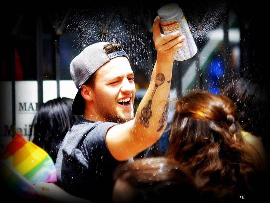Candid shot of a man spraying a dancing crowd of people with beer on Pride Day