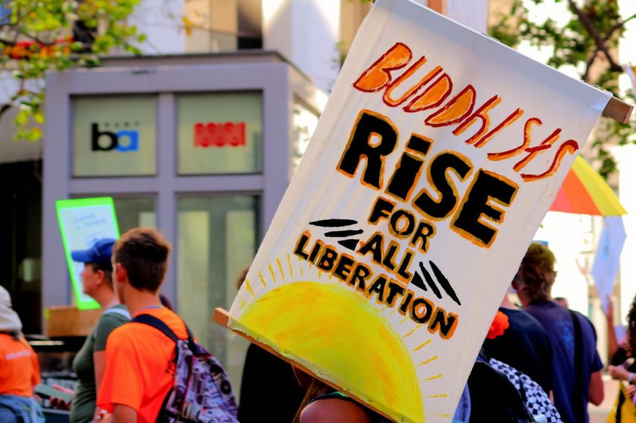 A sign that reads Buddhists rise for liberation at the Rise For Climate March in San Francisco