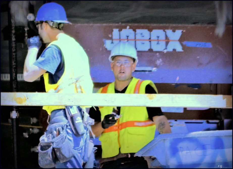 Construction workers on a scaffold, one eats a candy bar