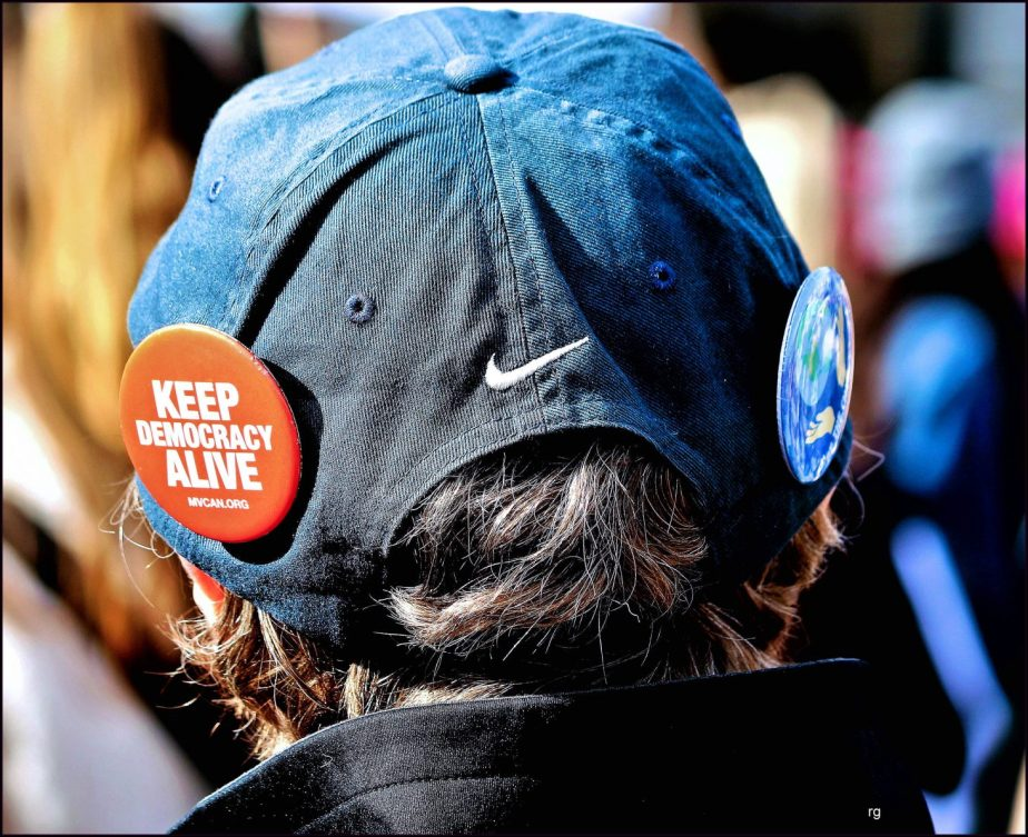 Photograph of a button on a hat worn by one of the men at the 2019 Women's March in San Francisco