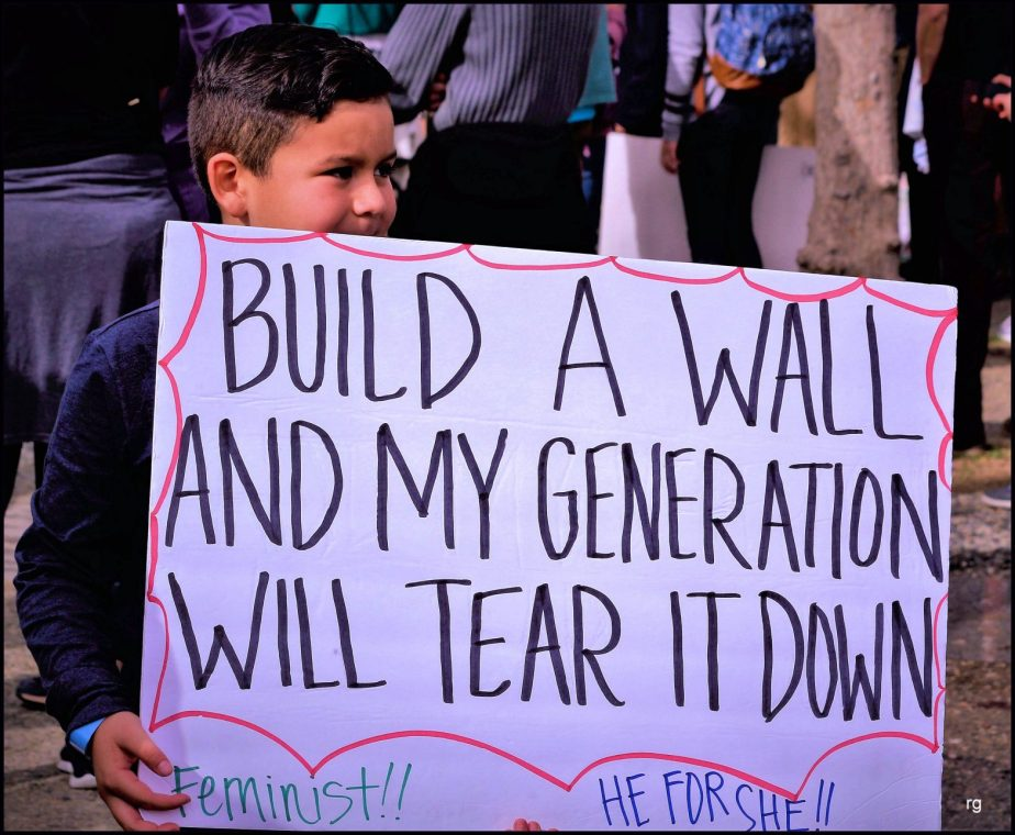 A Cild holds a sign at the 2019 Women's March in San Francisco that reads Build a Wall and My Generation Will Tear it Down