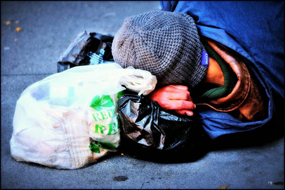 Photograph of a homeless man asleep on top of his bags