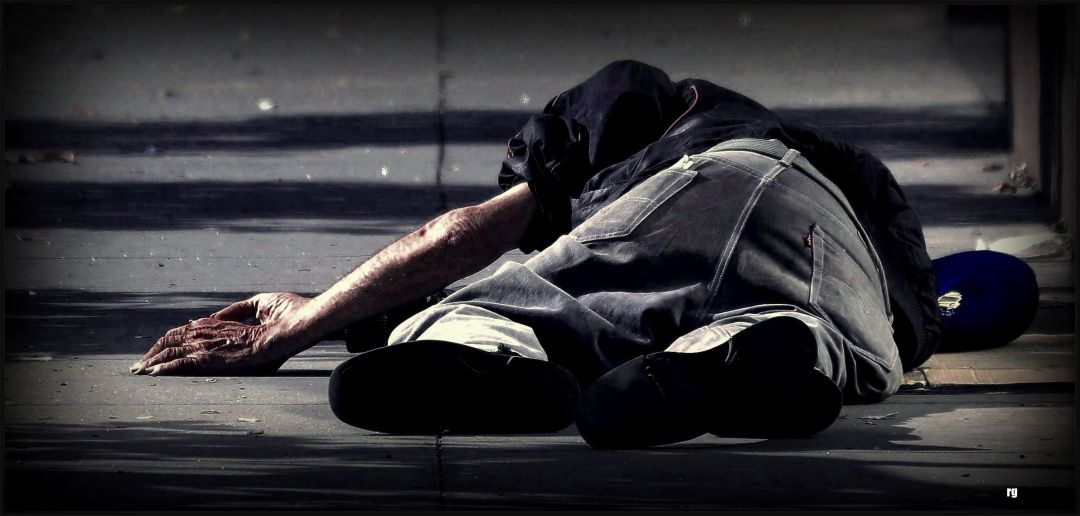 A homeless man asleep on concrete